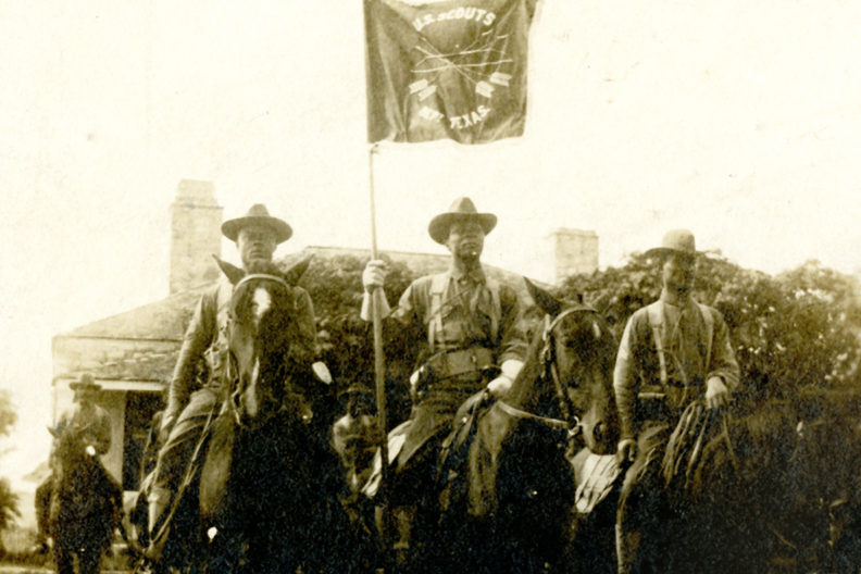 Three Native American scouts on horseback.