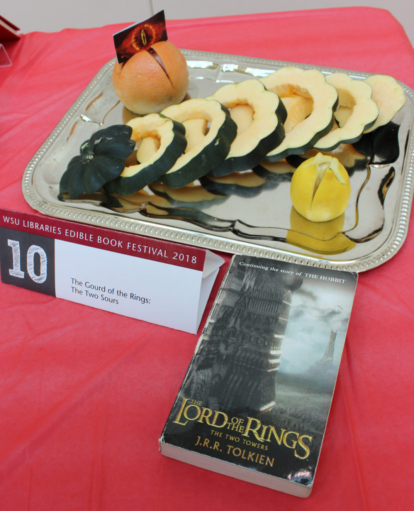 A sliced gourd, grapefruit and lemon presentation and 'The Lord of the Rings: The Two Towers' book.