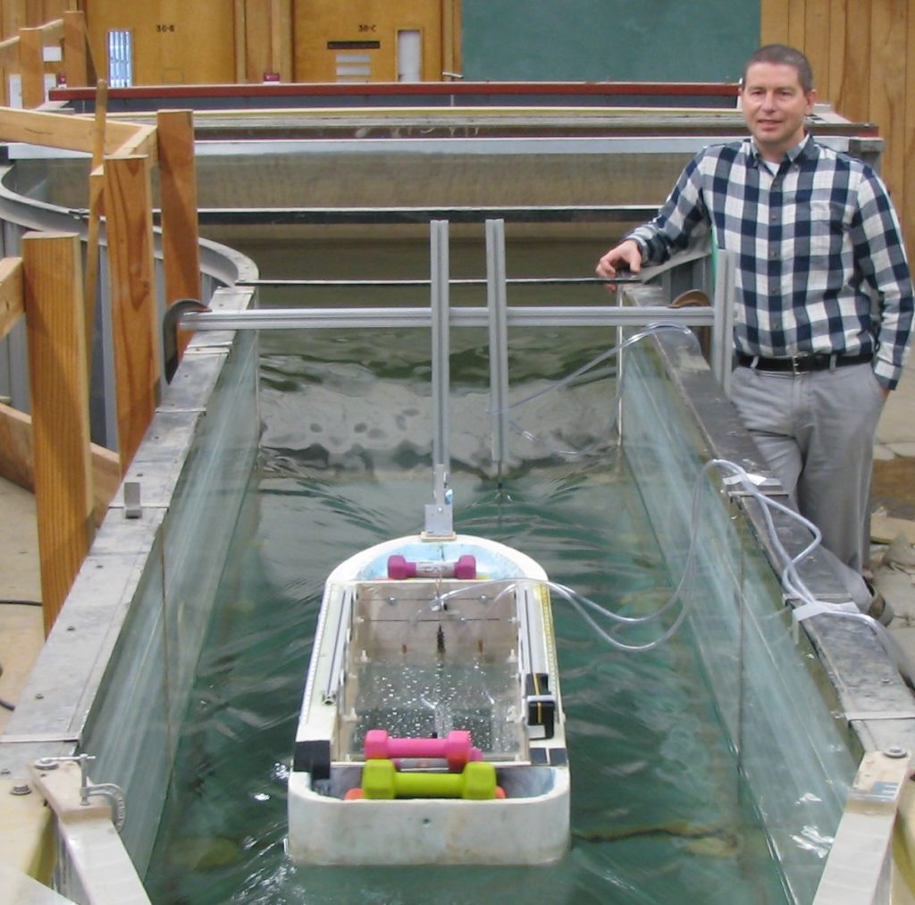 Matveev standing beside experimental boat in water channel at lab.
