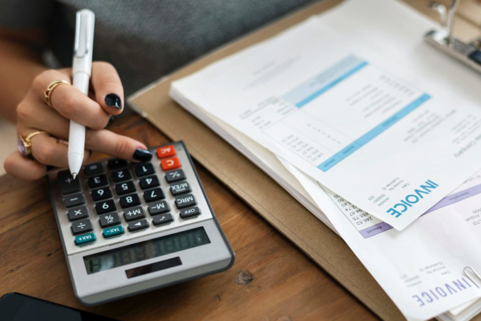 Closeup of desk and calculator as woman fills out insurance forms.