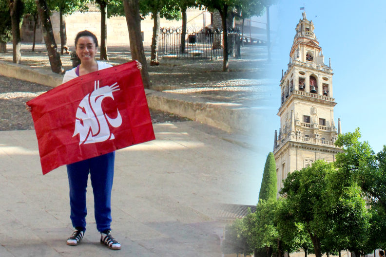 Alejandra Carranza standing with a WSU flag while traveling overseas.