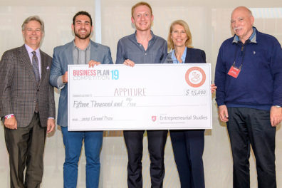 Appiture team members holding a giant check as they stand alongside dean and directors associated with the event.