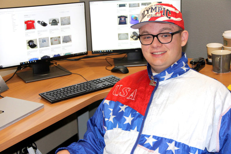 Dante Ludlow sitting next to a computer while wearing a 1996 Summer Olympics track suit.