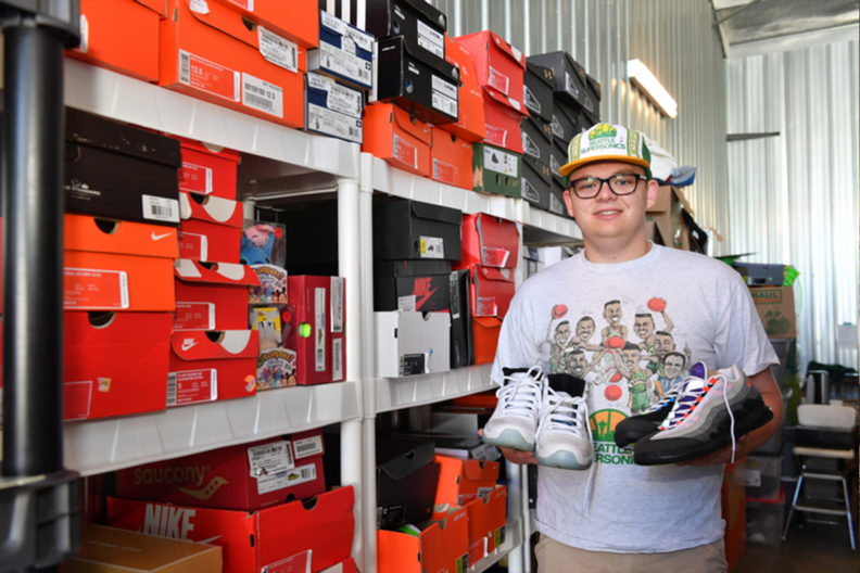 A photograph of Dante Ludlow in a warehouse with an inventory of shoe boxes