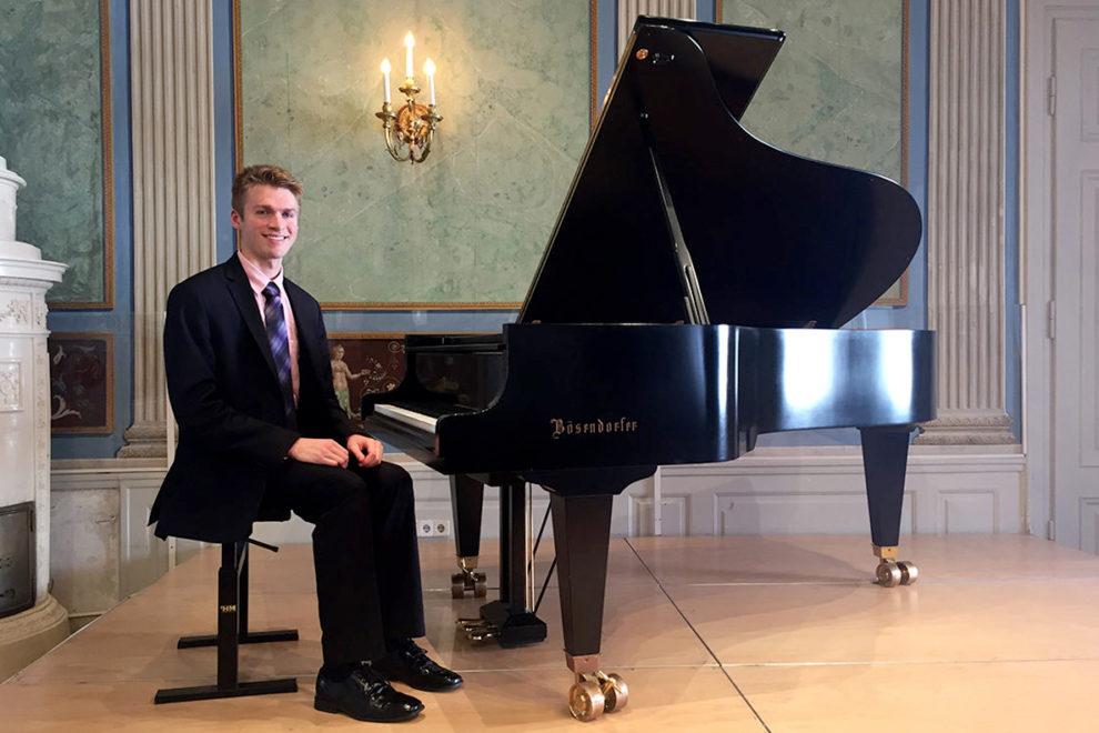Garrett Snedeker seated at piano.