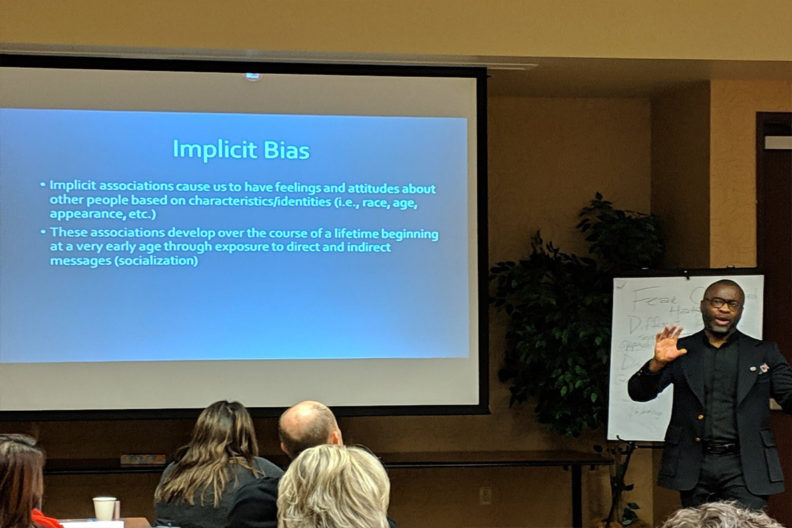 Obie Ford III discussing implicit bias with a slideshow presentation on a projector screen beside him.