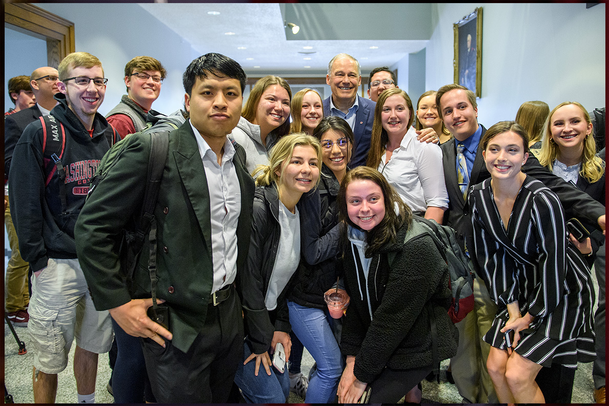 Gov. Jay Inslee posing with students outside the Bryan Hall Auditoriam
