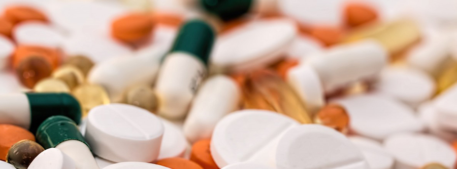 Closeup of a pile of various prescription pills.