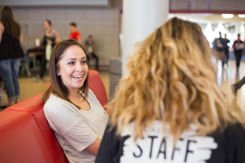 Student speaks with a staff member on campus.