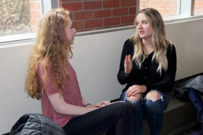 Alanna Quinn Jones and Caitlyn Aune talking in hallway.