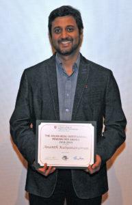 Ananth Kalyanaraman holding award.