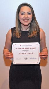 Hannah Zmuda holding award.