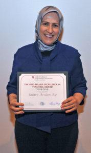 Sakire Arslan Ay holding award.