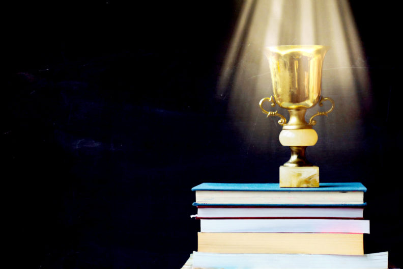 A golden trophy shines as it sits atop a pile of books.