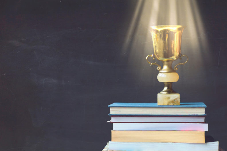 Golden trophy on pile of books, against blackboard, with sun rays over trophy; learning/achievement concept