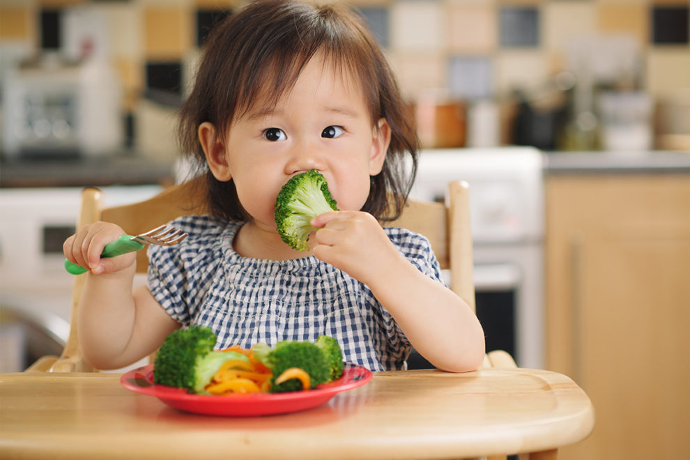 Toddler in high chair eating broccoli.