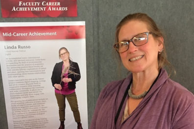 Linda Russo next to a sign displaying her research.