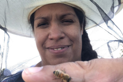 Melanie Kirby holding a bee on her finger.