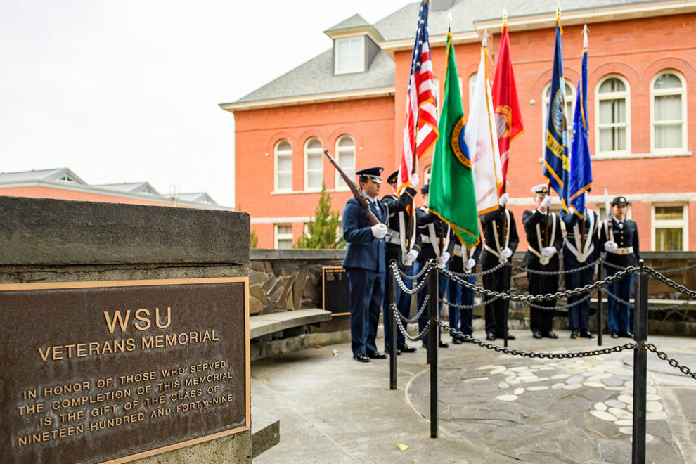 Soldiers holding flags during ceremony at WSU Veterans Memorial.