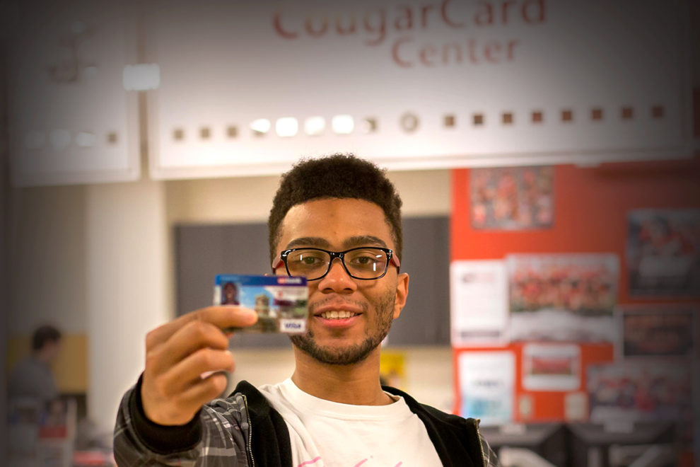 Student holding a CougarCard in front of the CougarCard Center.