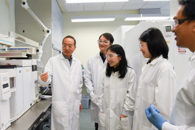 Lei and his team standing in a laboratory with lab coats.