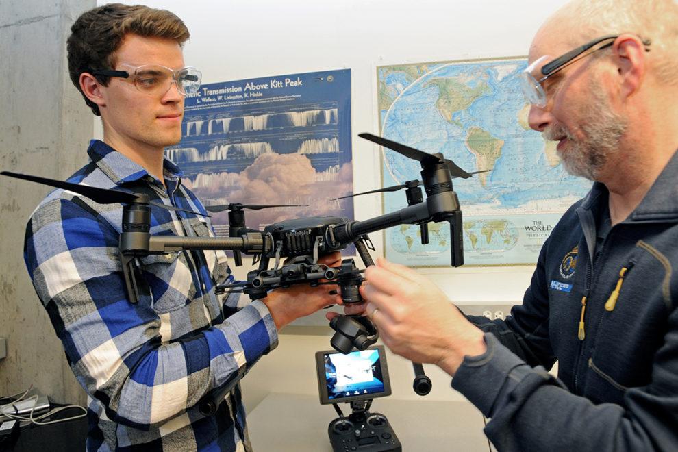 Gubsch and Walden adjusting a drone.
