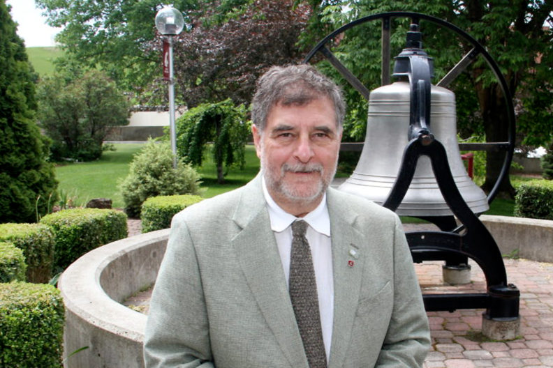 Closeup of Richard Zack in front of the WSUAA victory bell.