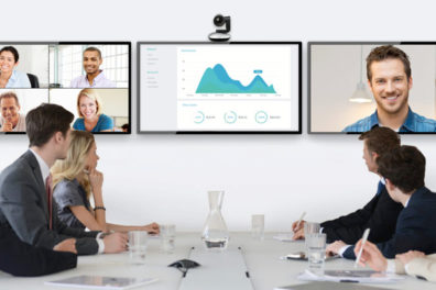 People in a conference room interacting with Zoom participants on screen.