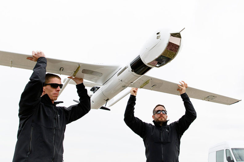 Two men holding a UAV by its wings.