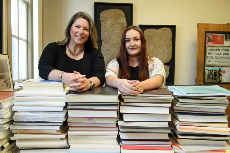 Tushingham and Fulkerson stand behind a large stack of books.
