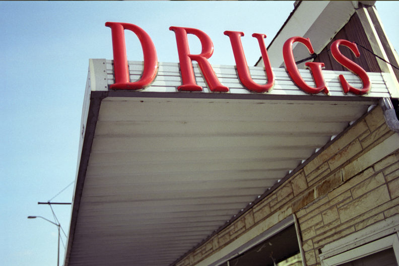 A photograph of an awning with the sign DRUGS in big red letters