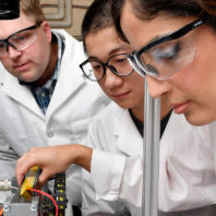 Three scientists looking at a work table.