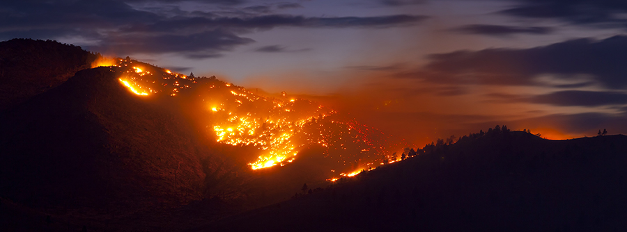 Aerial view as wildfires fill the night sky on a mountain ridge.