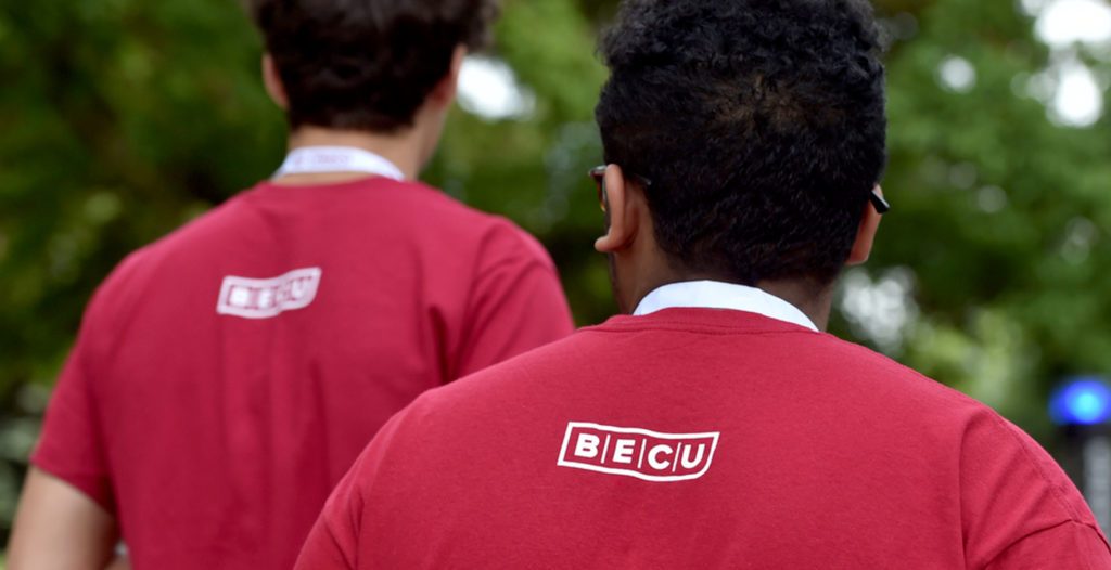 Students wearing shirts with BECU logo printed on the back.