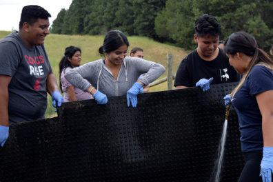 Students holding up a mat and spraying it clean with a hose.
