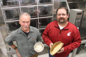 Craig Morris, director of the USDA Western Wheat Quality Laboratory, left, and WSU spring wheat breeder Mike Pumphrey hold samples of Ryan grain and fresh noodles.