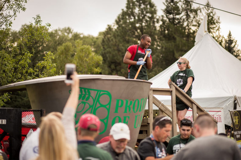 A photograph of the world's largest bowl of lentil chili being stirred by a man with a long wooden spoon at a festival.