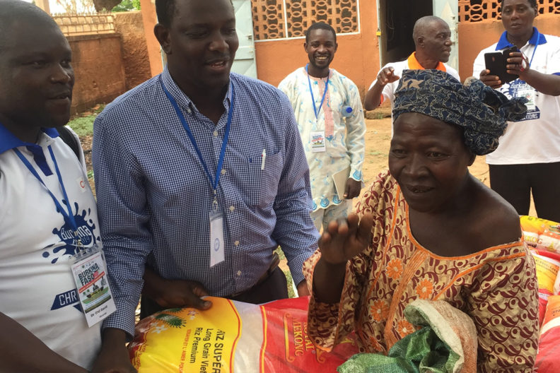 David Oni, left, and Abel Saba, right, help distribute the two tons of rice they brought to Burkina Faso.