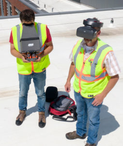 A drone operator controls a drone and someone else wears goggles as a drone inspects a construction project.
