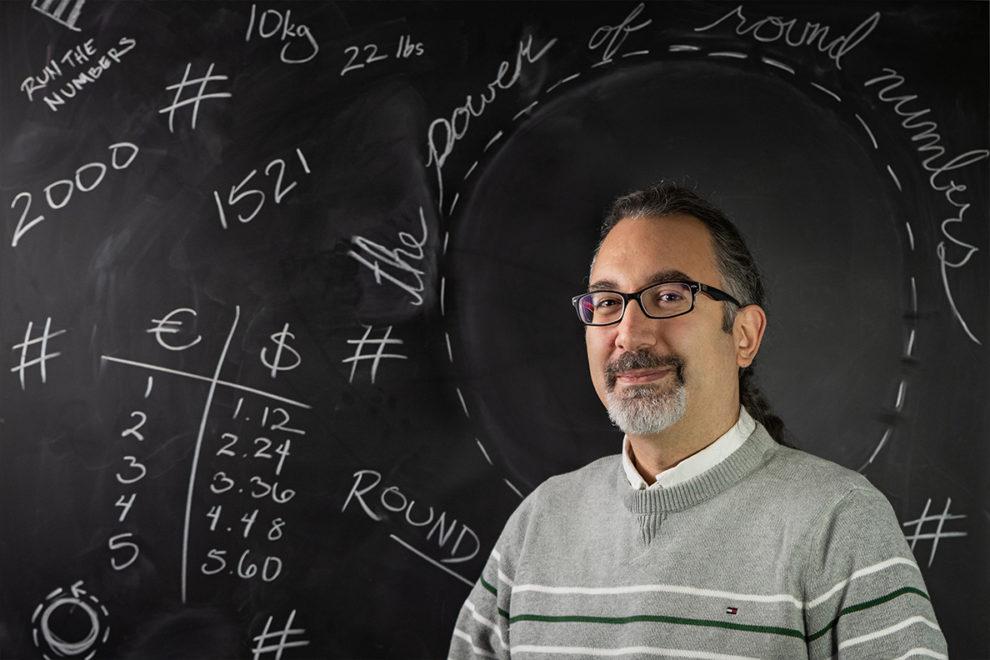 Kunter Gunasti in front of a chalkboard.