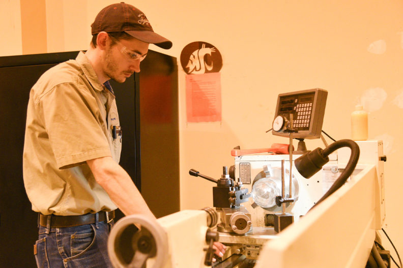 WSU Tri-Cities student engineer Bryan Chronister works in the engineering high bay to craft an instrument prototype.