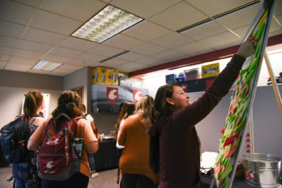 A WSU Tri-Cities student posts up an idea for what to include as a resource for the MOSAIC Center for Student Inclusion during a soft opening event last spring for the center.