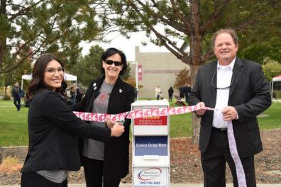 Three people cut the ribbon on WSU Tri-Cities' first ballot box.