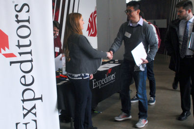 Two people shake hands during a career expo.