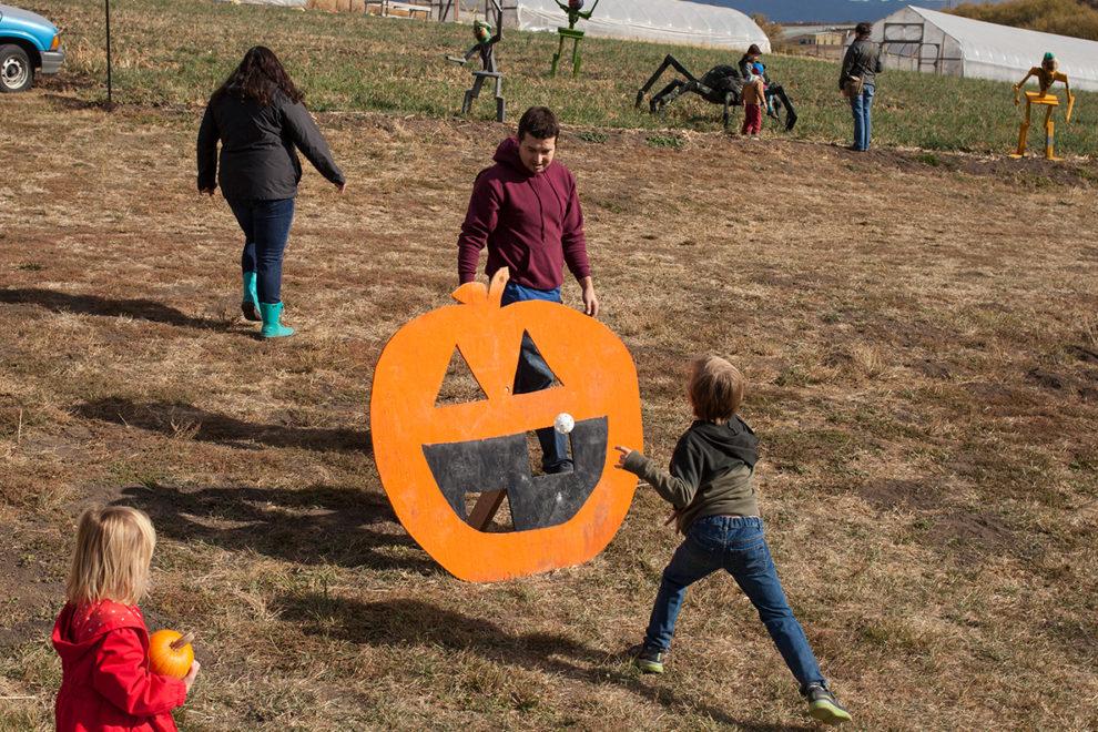 Kids playing pumpkin toss.