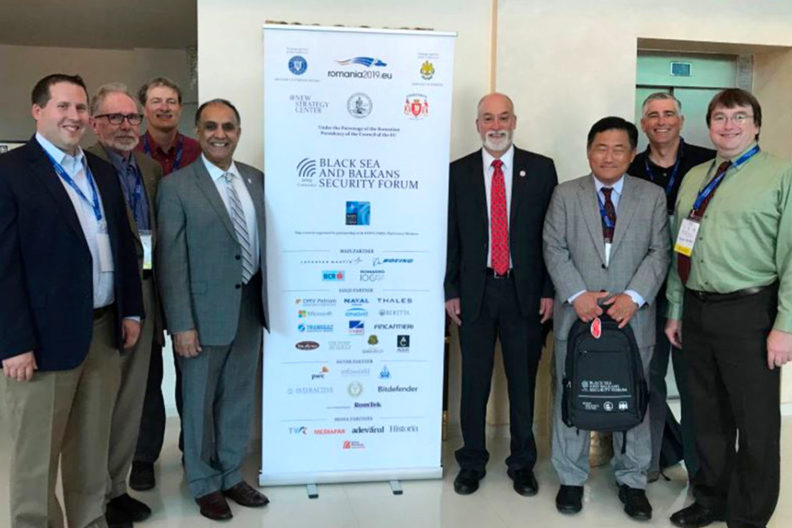Group of forum participants standing next to a banner.