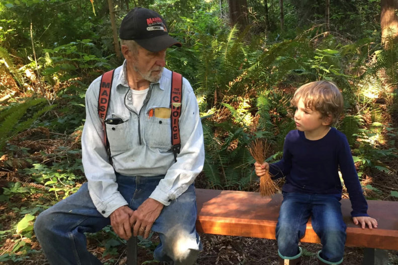 A man and a child sit on a log in a forest.