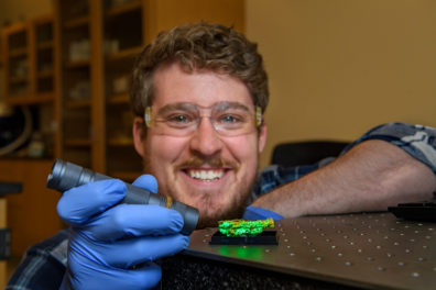 A researcher shines a light on a mineral sample.