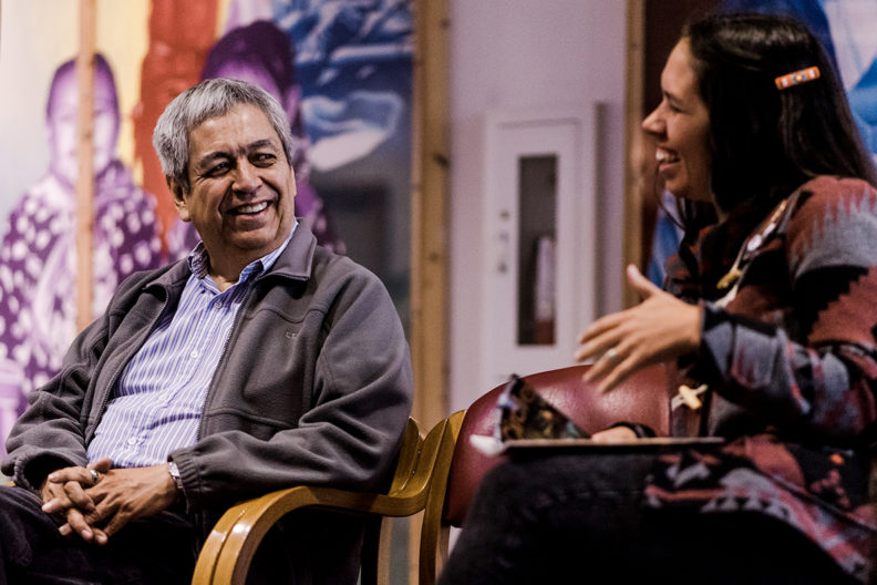 Two people sitting in chairs and smiling at one another.