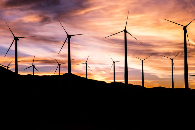 Several windmills stand on a hillside during sunset.